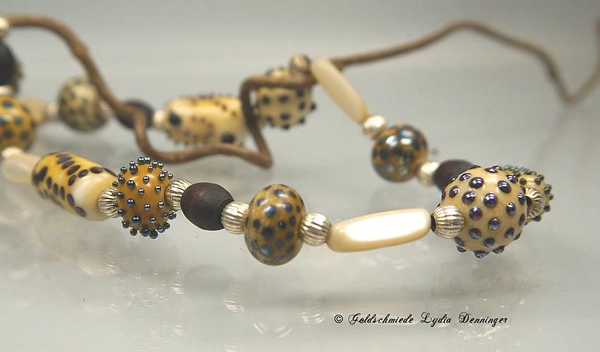 Glasperlen mit  Holzperlen, Goldperlen und Perlmut kombiniert.
