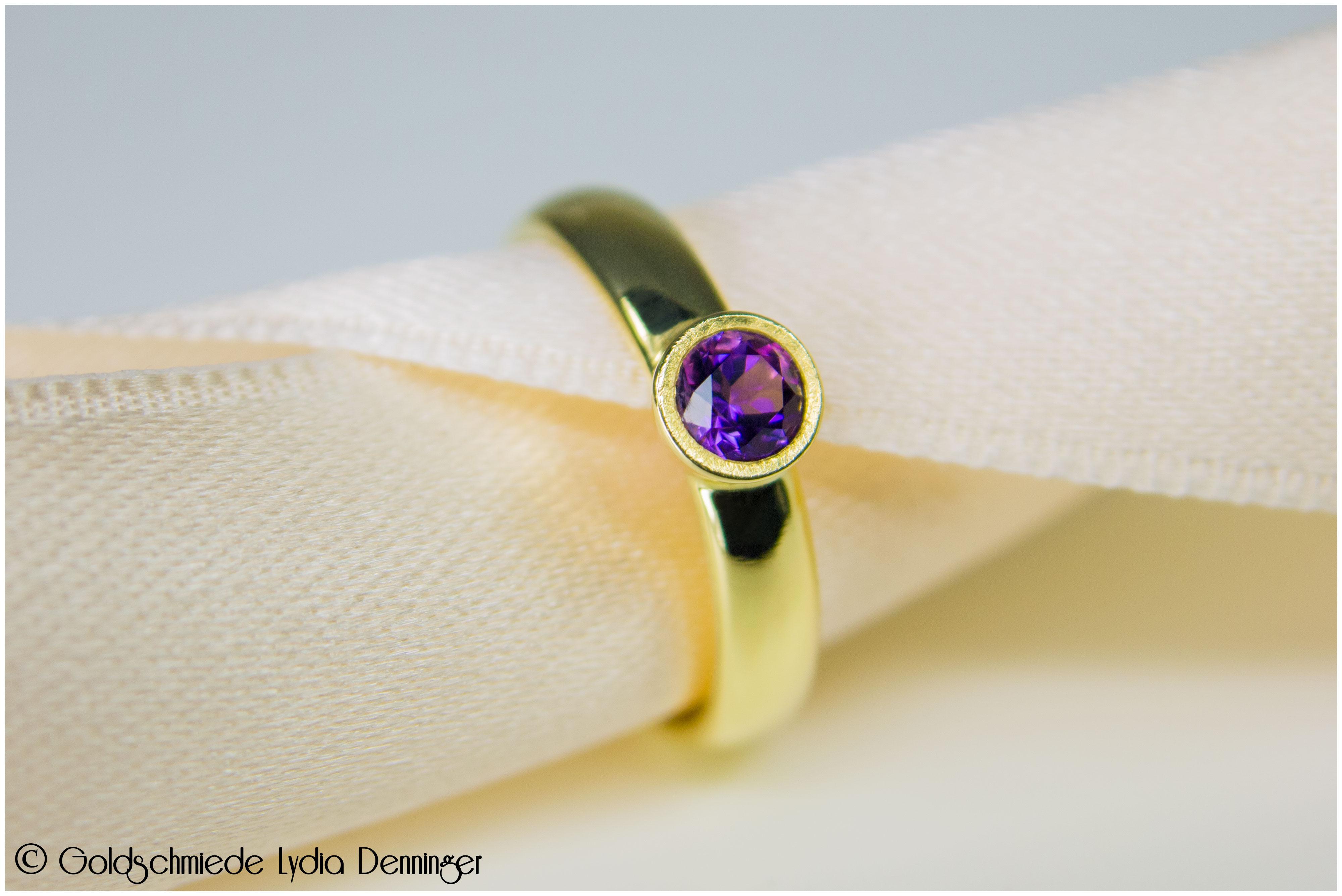 Ring 585/- Gelbgold, in die Solitärfassung wurde ein Amethyst eingebettet und die Glanzkante wurde eismattiert