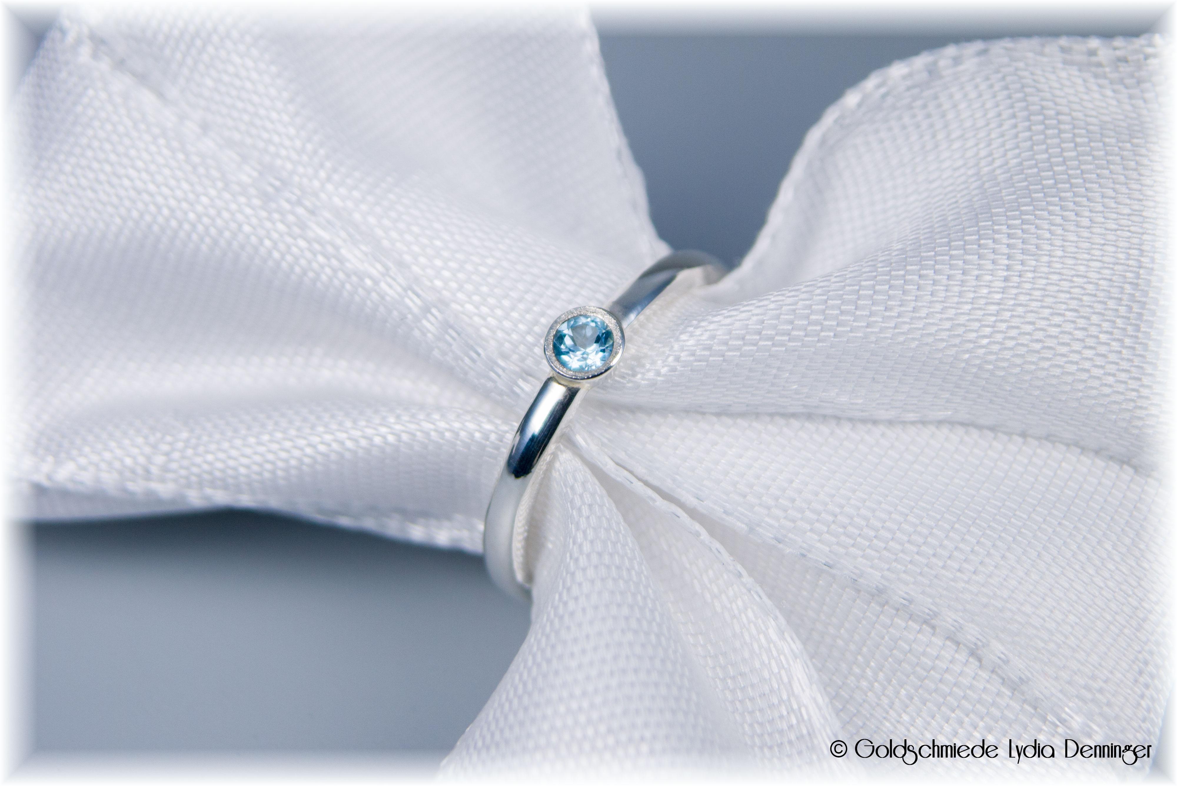 Umarbeitung - auf einen glatten Silberring wurde eine Fassung mit eisblauen Topas geschmiedet. Die Kante wurde eismattier